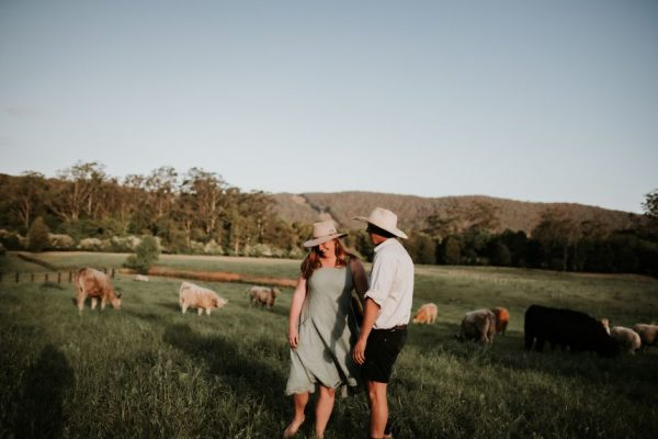 Tim and Hannah, founders and first generation farmers at The Food Farm standing in a paddock with cows in background
